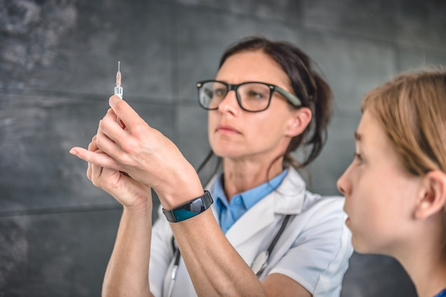 医者は患者に注射するワクチンを準備します
