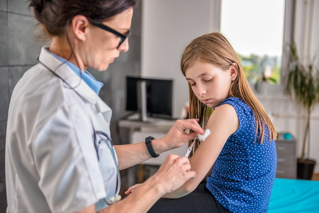 Доктор дает молодой девушке прививки