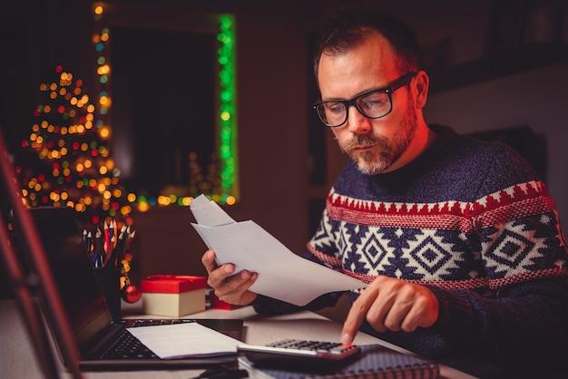 請求書と税金費用を計算する男