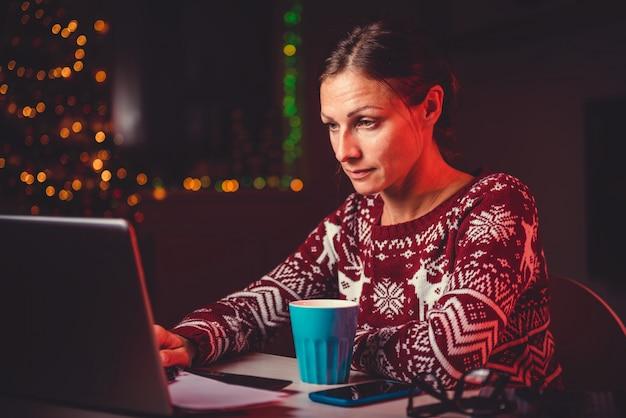 夜遅くまで働いてラップトップを使用している女性