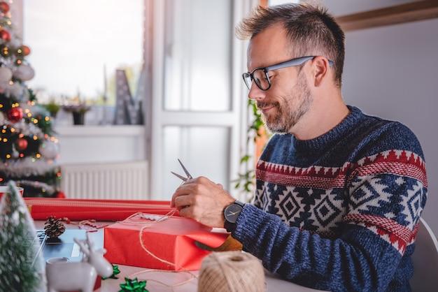 クリスマスプレゼントを包む男性