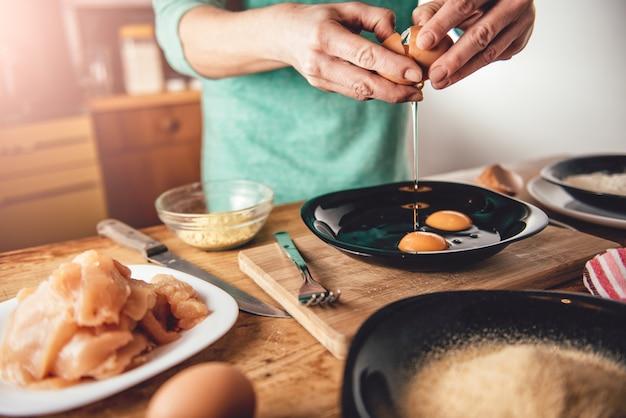 女性の料理と卵を皿に割る