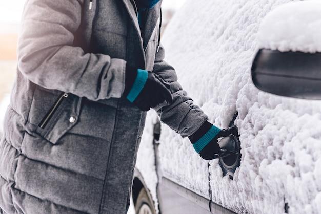 雪に覆われた車を開く女性
