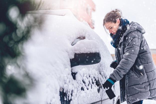Женщина открывает автомобиль, покрытый снегом