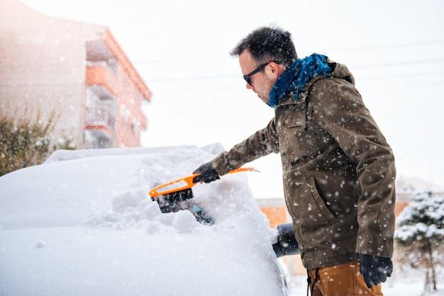 雪に覆われた車の掃除人