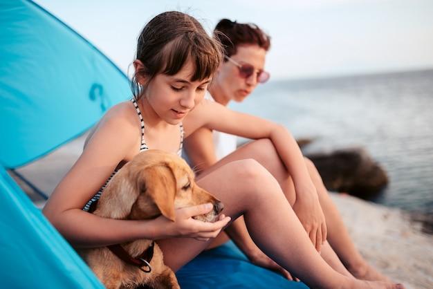 母とビーチテントの中に座って彼女の犬を抱きしめる少女