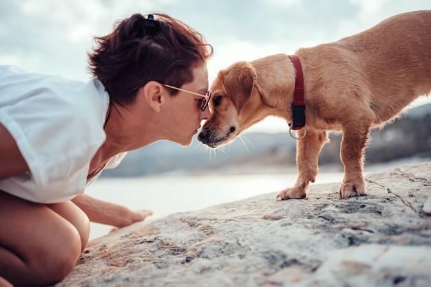 犬はビーチで女性と寄り添う