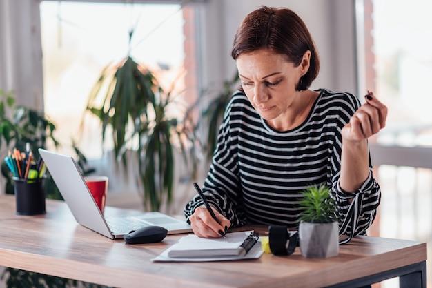 ノートにメモを書く女性