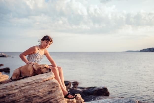 Девушка обнимает свою собаку, сидя на скале у моря