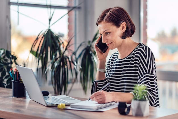 オフィスでスマートフォンで話している女性