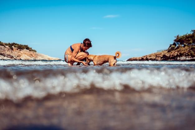 Женщина расплачивается с собакой на пляже