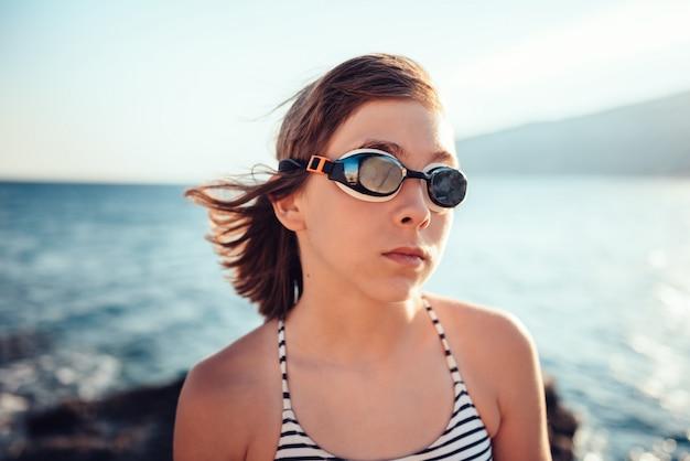 Портрет девушки носить очки для плавания на пляже
