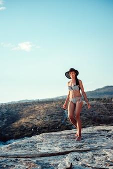 Бикини женщины и шляпа солнца гуляя на пляж