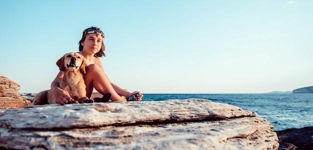 Девушка обнимает свою собаку, сидя на скалистом пляже