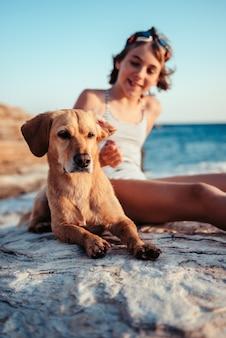 Собака лежит на пляже с девушкой