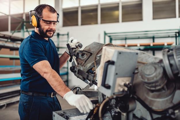 Заводской рабочий работает ленточнопильный станок