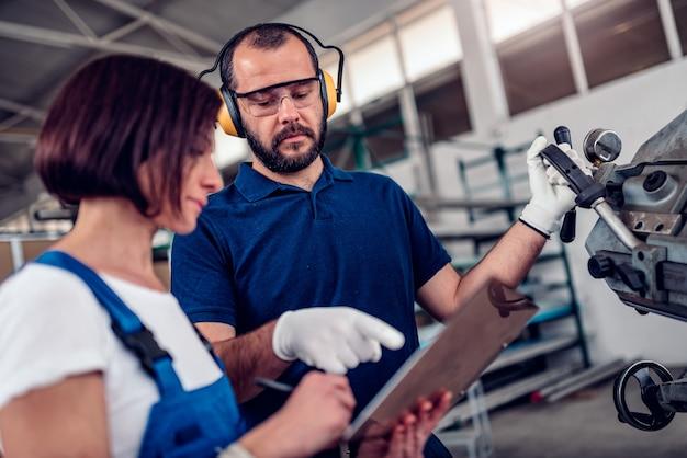 帯鋸切断機のオペレーターは、事務員と一緒に撮影