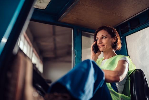 Оператор вилочного погрузчика женщина разговаривает по телефону в транспортном средстве