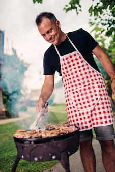 Мужчины в фартуке готовят мясо на заднем дворе