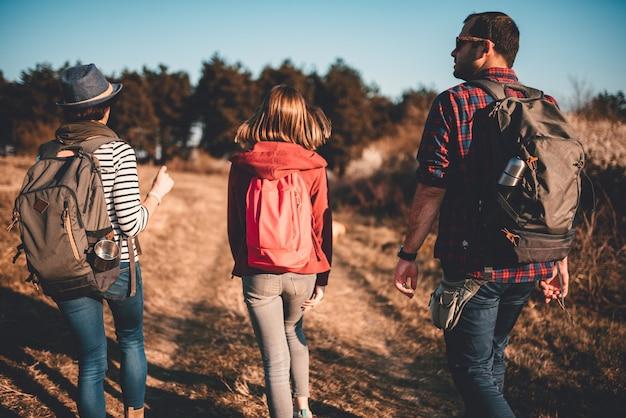 汚れた道路でのハイキングの家族の背面図
