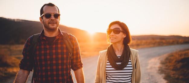 日没時に未舗装の道路で幸せなハイキングカップル