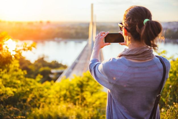 スマートフォンで屋外の写真を撮る女性