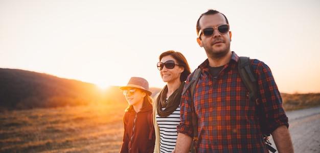 幸せな家族が日没時に未舗装の道路でハイキング