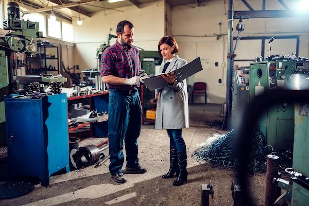 ギアシャフトの直径を測定する機械工と相談する女性エンジニア