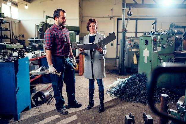 工場で機械工と話している女性の安全検査官