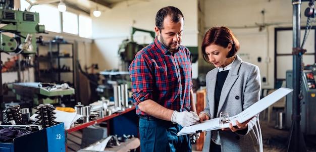 女性エンジニアが機械工と相談し、青写真を分析