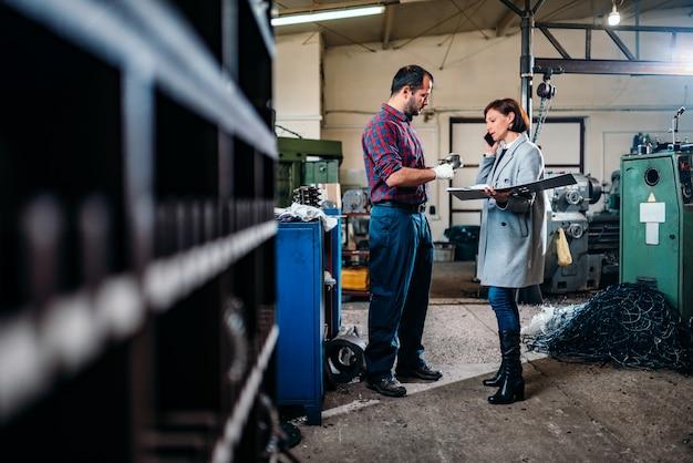 機械工の側に立って、クライアントと電話で話している女性エンジニア