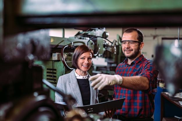 Машинист обсуждает с женщиной-супервайзером на заводе