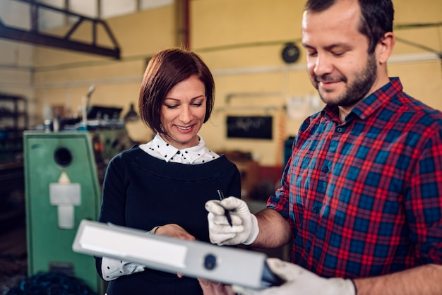 Рабочий на фабрике подписывает документ