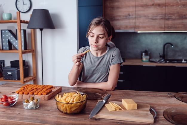 Девочка ест картофель фри