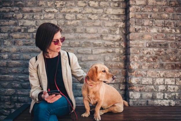 Женщина сидит на скамейке и гладит свою собаку