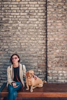 ベンチに座っていると彼女の犬をかわいがる女性