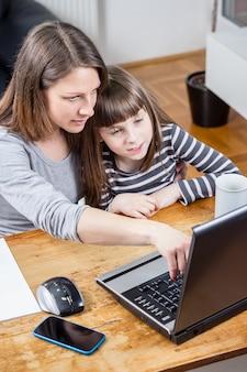 Мать и дочь, используя ноутбук