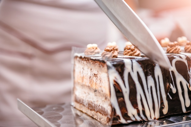 Шеф-кондитер берет кусок торта