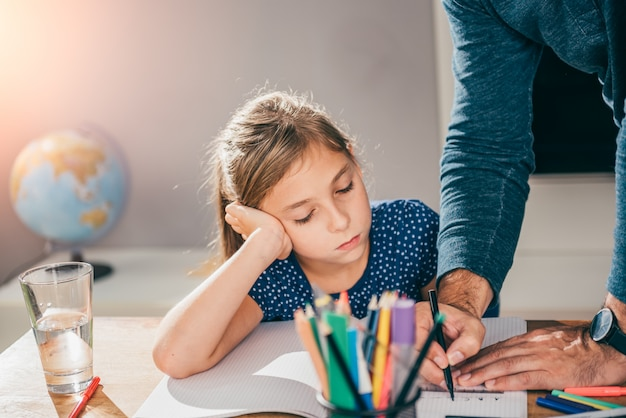 Отец помогает дочери закончить домашнее задание