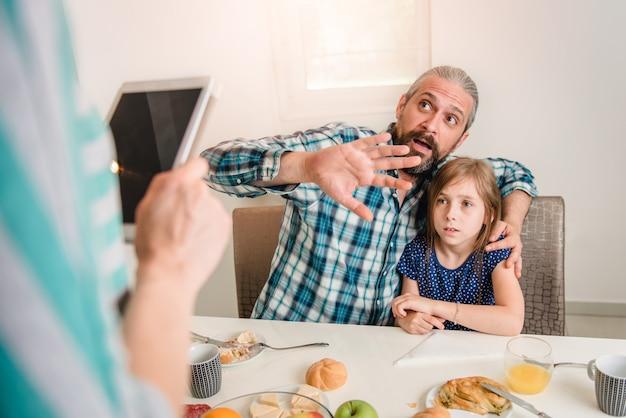 母はタブレットについて娘と父親を批判します