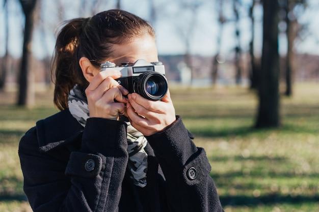 古いアナログカメラで写真を撮る女性
