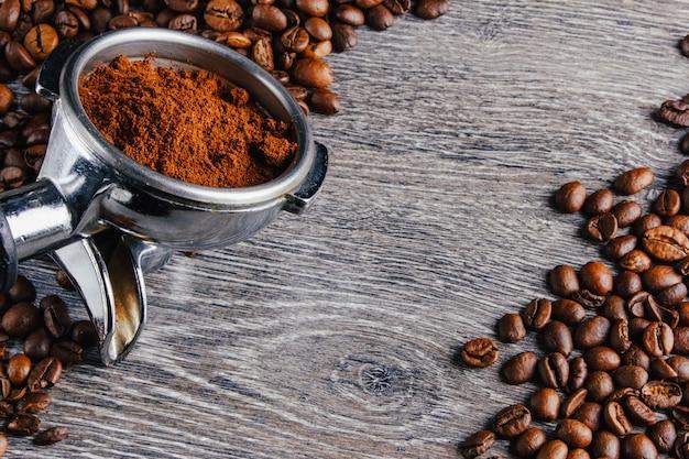 Портафильтр и кофейные зерна на фоне дерева