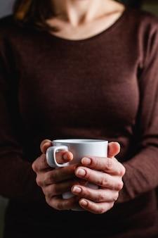 Женщина держит чашку кофе