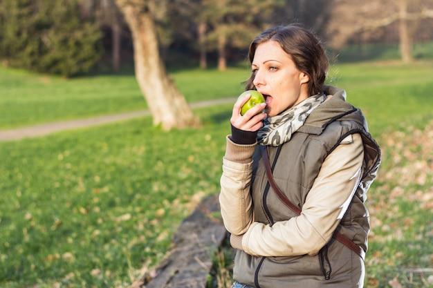 Женщина ест яблоко