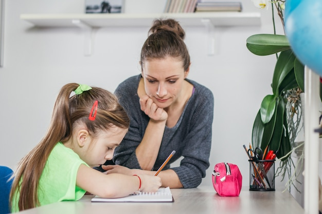 Мать помогает дочери с домашней работой