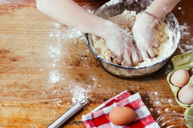 Девушка на кухне играет с мукой