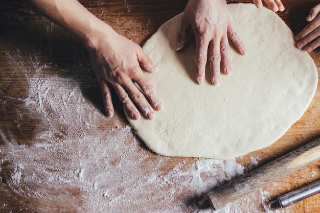 Женщина руками замешивает тесто на столе