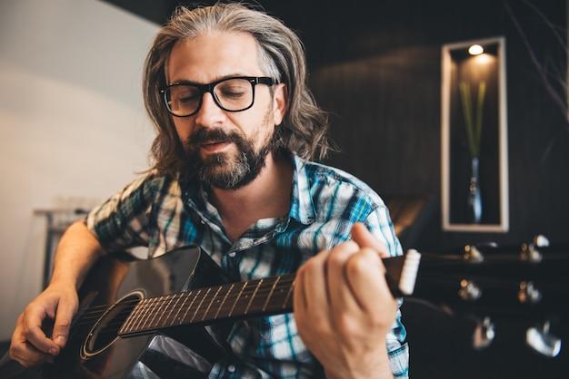 ソファに座って、自宅でギターを弾く男