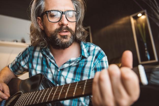 Человек сидит на диване и играет на гитаре у себя дома