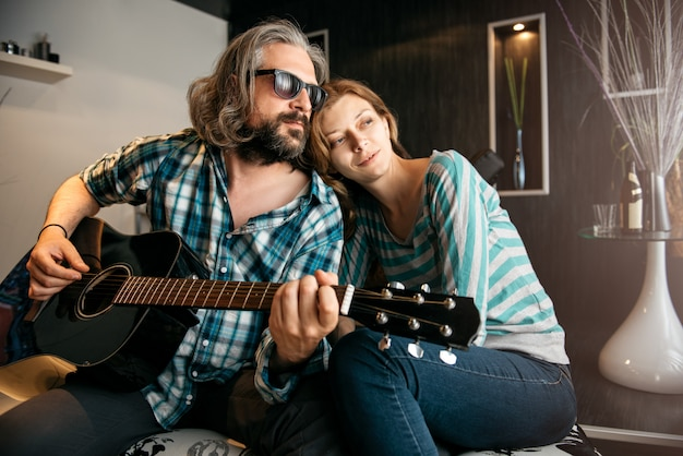 Романтический мужчина играет на гитаре для своей женщины